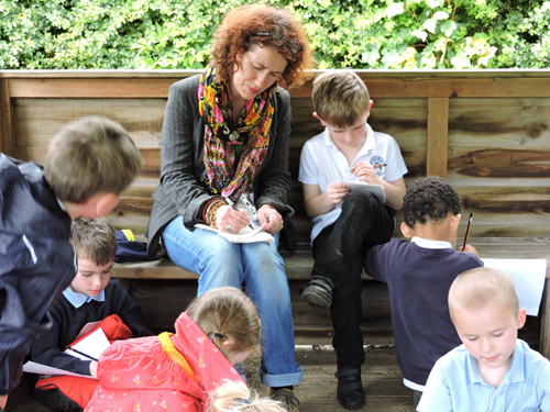 Artist Sally Todd and children creating amulet poems