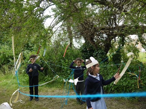 Children using woolen thread and strips of paper called introducing the forest
