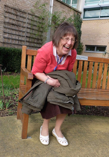 Mavis, volunteer sitting on a bench laughing
