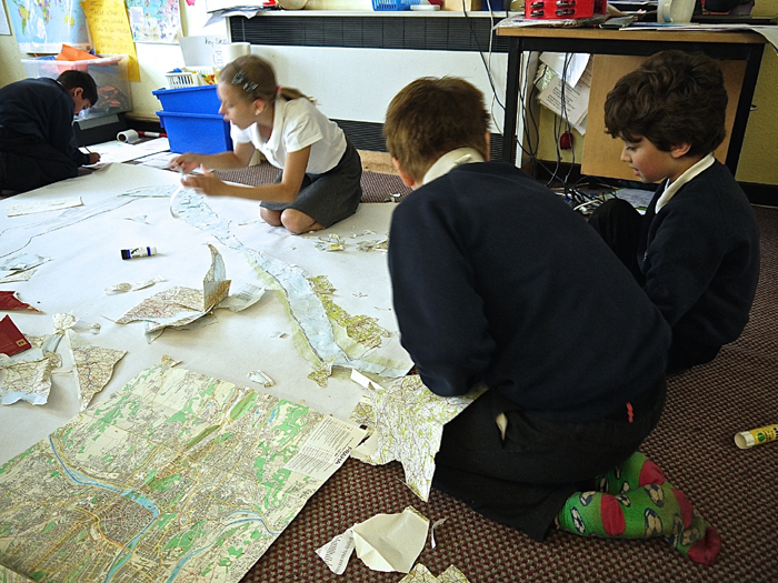 Children work on their fantastical map kneeling on the ground